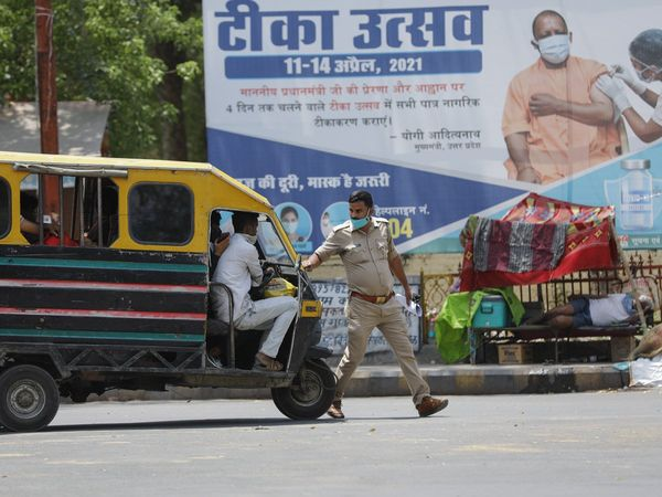 A policeman stops an auto-rickshaw at a check point during a weekend lockdown in Prayagraj Photo Credit AP